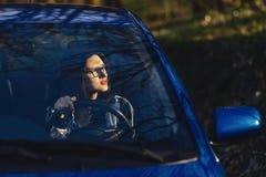 La ragazza sta sedendosi alla ruota dell'automobile immagine stock libera da diritti