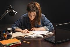 La ragazza sta sedendosi alla tavola ed allo studio immagini stock libere da diritti