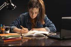 La ragazza sta sedendosi alla tavola ed allo studio immagini stock