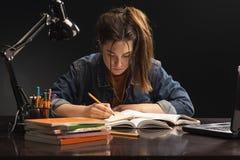 La ragazza sta sedendosi alla tavola ed allo studio fotografie stock libere da diritti