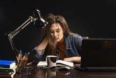 La ragazza sta sedendosi alla tavola ed allo studio fotografia stock libera da diritti