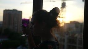 La ragazza sta sedendosi dalla finestra con un vetro in sue mani, piene d'ammirazione il tramonto nella città Movimento lento video d archivio