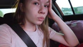 La ragazza sta sedendosi nel sedile posteriore dell'automobile, indossante una cintura di sicurezza stock footage