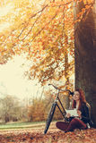 La ragazza sta sedendosi sotto l'albero con la compressa Fotografia Stock Libera da Diritti