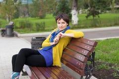 La ragazza sta sedendosi su un banco di sosta Fotografia Stock Libera da Diritti