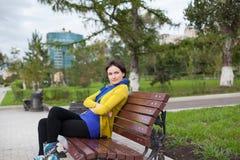 La ragazza sta sedendosi su un banco di sosta Fotografie Stock Libere da Diritti