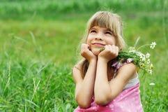 La ragazza sta sedendosi sul campo Fotografie Stock