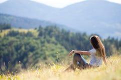 La ragazza sta sedendosi sul fianco di una montagna Fotografia Stock Libera da Diritti