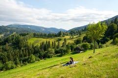 La ragazza sta sedendosi sul fianco di una montagna vicino alla vecchia casa Fotografia Stock