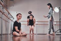 La ragazza sta sedendosi sul pavimento mentre i suoi altri compagni di classe che fanno gli esercizi con l'istruttore fotografia stock