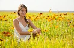 La ragazza sta sedendosi sul prato dei fiori fotografia stock
