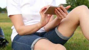La ragazza sta sedendosi sull'erba verde e lavora ad Internet tramite il vostro smartphone Essi tutti i sociale ed affare stock footage
