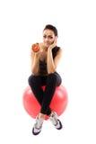 La ragazza sta sedendosi sulla palla di forma fisica e sta tenendo un pomodoro Fotografia Stock Libera da Diritti