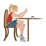 La ragazza sta sedendosi in un caffè ed in una scrittura Immagini Stock
