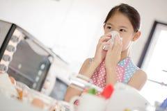La ragazza sta soffiando il suo naso, allergico per flour Immagine Stock