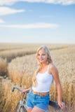 La ragazza sta sorridendo nel campo con la retro bici Fotografie Stock Libere da Diritti