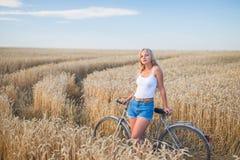 La ragazza sta sorridendo nel campo con la retro bici Immagine Stock