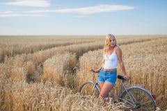 La ragazza sta sorridendo nel campo con la retro bici Fotografie Stock