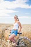 La ragazza sta sorridendo nel campo con la retro bici Fotografia Stock Libera da Diritti