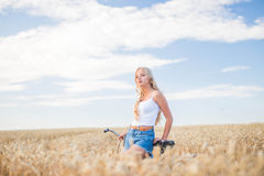 La ragazza sta sorridendo nel campo con la retro bici Fotografia Stock
