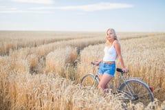 La ragazza sta sorridendo nel campo con la retro bici Immagine Stock Libera da Diritti