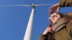 La ragazza sta sotto le turbine giranti del mulino a vento e esamina la distanza su fondo del primo piano del cielo video d archivio