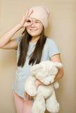 La ragazza sta spazzolando il suo orsacchiotto Immagini Stock