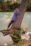La ragazza sta stando pendente contro un grande piegamento giù l'albero in acqua in autunno Immagine Stock Libera da Diritti