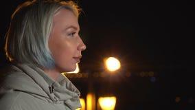 La ragazza sta stando in rivestimento dello schermo, guardante nella distanza nella città di notte video d archivio