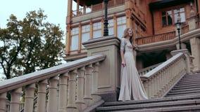 La ragazza sta stando su una grande scala di pietra nei precedenti del palazzo stock footage
