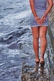 La ragazza sta stando sull'orlo del pilastro Immagini Stock