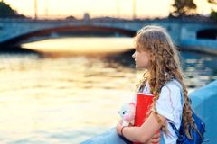 La ragazza sta stando vicino al fiume nella città al tramonto immagine stock libera da diritti