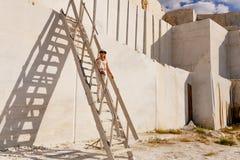 La ragazza sta su un'alta scala nella via Fotografie Stock