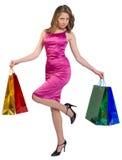 La ragazza sta sui sacchetti della spesa di una tenuta della gamba Immagini Stock Libere da Diritti