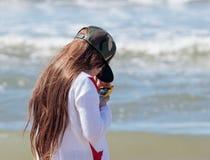 La ragazza sta sulla spiaggia e sull'esame del telefono cellulare Fotografia Stock