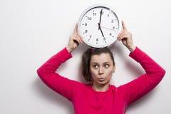 La ragazza sta tenendo l'orologio sopra la sua testa Concetto di tempo Tempo e donna sul fondo bianco della parete orologio nelle Fotografia Stock Libera da Diritti