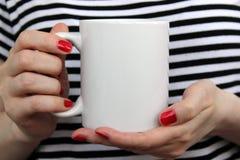 La ragazza sta tenendo la tazza bianca in mani Fotografia Stock
