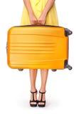 La ragazza sta tenendo la valigia arancio Fotografie Stock Libere da Diritti