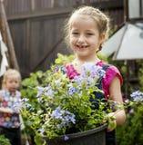 La ragazza sta tenendo un fiore in un giardino Fotografia Stock
