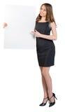 La ragazza sta tenendo un grande tabellone per le affissioni vuoto, mostra Immagine Stock