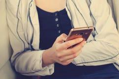 La ragazza sta tenendo un telefono cellulare Primo piano immagine stock libera da diritti