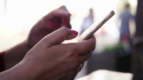 La ragazza sta tenendo un telefono di tocco in sue mani, sta guidando il suo dito attraverso lo schermo Primo piano HD, 1920x1080 video d archivio