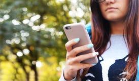 La ragazza sta tenendo un telefono, lei scrive il testo immagine stock libera da diritti