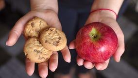 La ragazza sta tenendo una mela ed i biscotti, primo piano archivi video