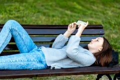 La ragazza sta trovandosi sul banco di estate in natura del parco Una scolara sta riposando dopo la scuola, di svago nell'istitut Fotografia Stock Libera da Diritti
