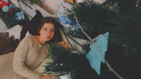 La ragazza sta trovandosi sul letto sui precedenti dell'albero di Natale Nuovo anno stock footage