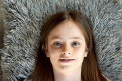 La ragazza sta trovandosi sul pavimento Fotografie Stock
