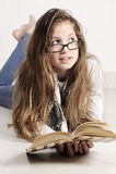 La ragazza sta trovandosi sul pavimento con un libro Fotografia Stock Libera da Diritti