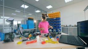 La ragazza sta vicino ad una tavola con i giocattoli, indossanti 360 vetri di VR 4K archivi video