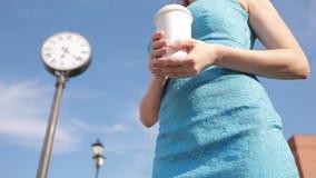 La ragazza sta vicino all'orologio ed al caffè bevente attesa video d archivio